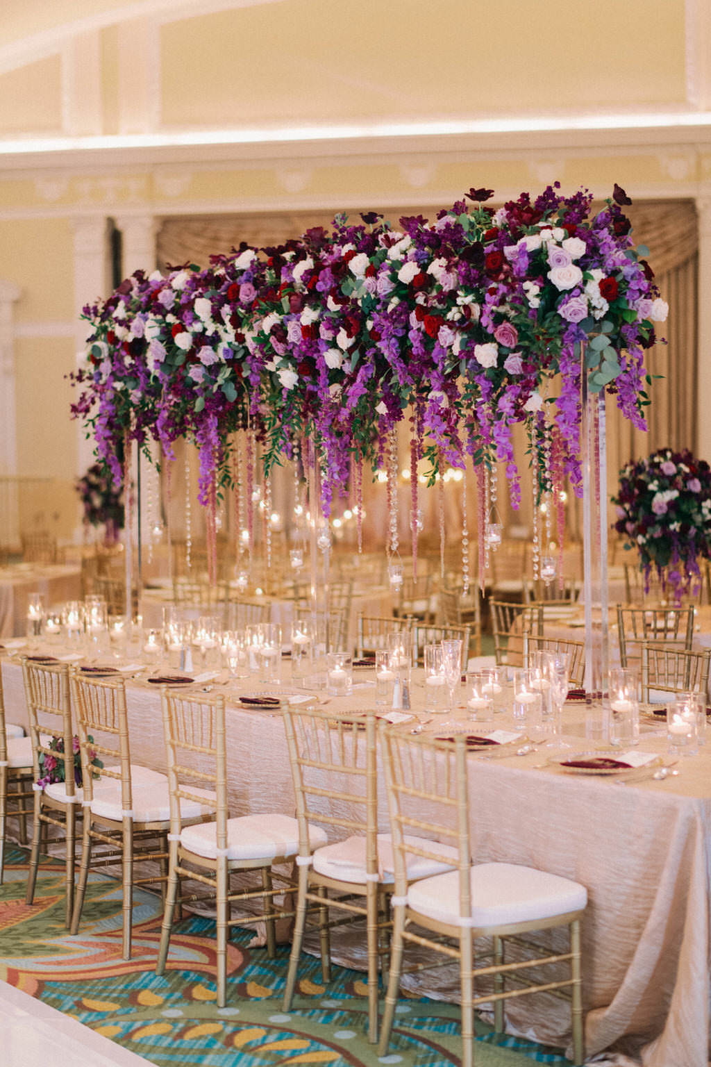 Elegant, Extravagant Wedding Reception Decor Portrait, Long Table with Gold Linen, Gold Chiavari Chairs, Tall Purple, Plum, Lilac, Red Greenery and Purple Hanging Amaranthus Floral Centerpiece | Downtown St. Pete Hotel Ballroom Wedding Venue The Vinoy Renaissance