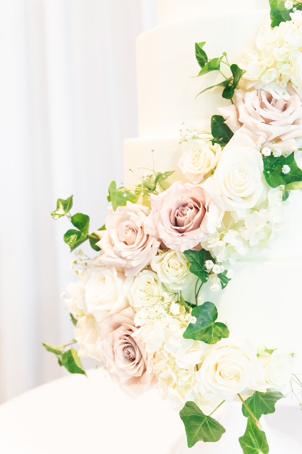 Classic Round White Wedding Cake with Cascading Blush Pink and White Roses, Baby's Breath and Greenery Leaves Flowers