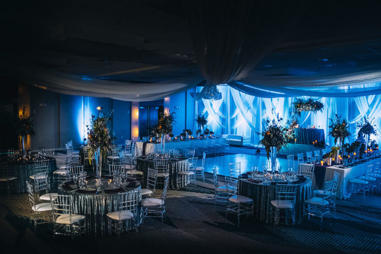 Unique Modern Contemporary Dark and Dramatic Wedding Reception Decor, Linen Drapery, Round and Long Feasting Tables, Blue Tablecloths, Clear Acrylic Ghost Chiavari Chairs, Tall Glass Vases with Unique Floral Centerpieces, Blue Uplighting | Tampa Bay Boutique Wedding Venue Hotel Alba | Wedding Planner Special Moments Event Planning | Wedding Rentals and Chair Decor Gabro Event Services