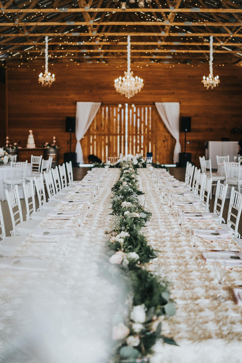 INSTAGRAM Rustic Chic Barn Wedding Reception Decor, Long Feasting Table with Greenery Garland Table Runner with Ivory Roses, White Chiavari Chairs, Crystal Chandeliers   Tampa Wedding Venue Rafter J Ranch   Tampa Bay Wedding Planner Kelly Kennedy Weddings and Events