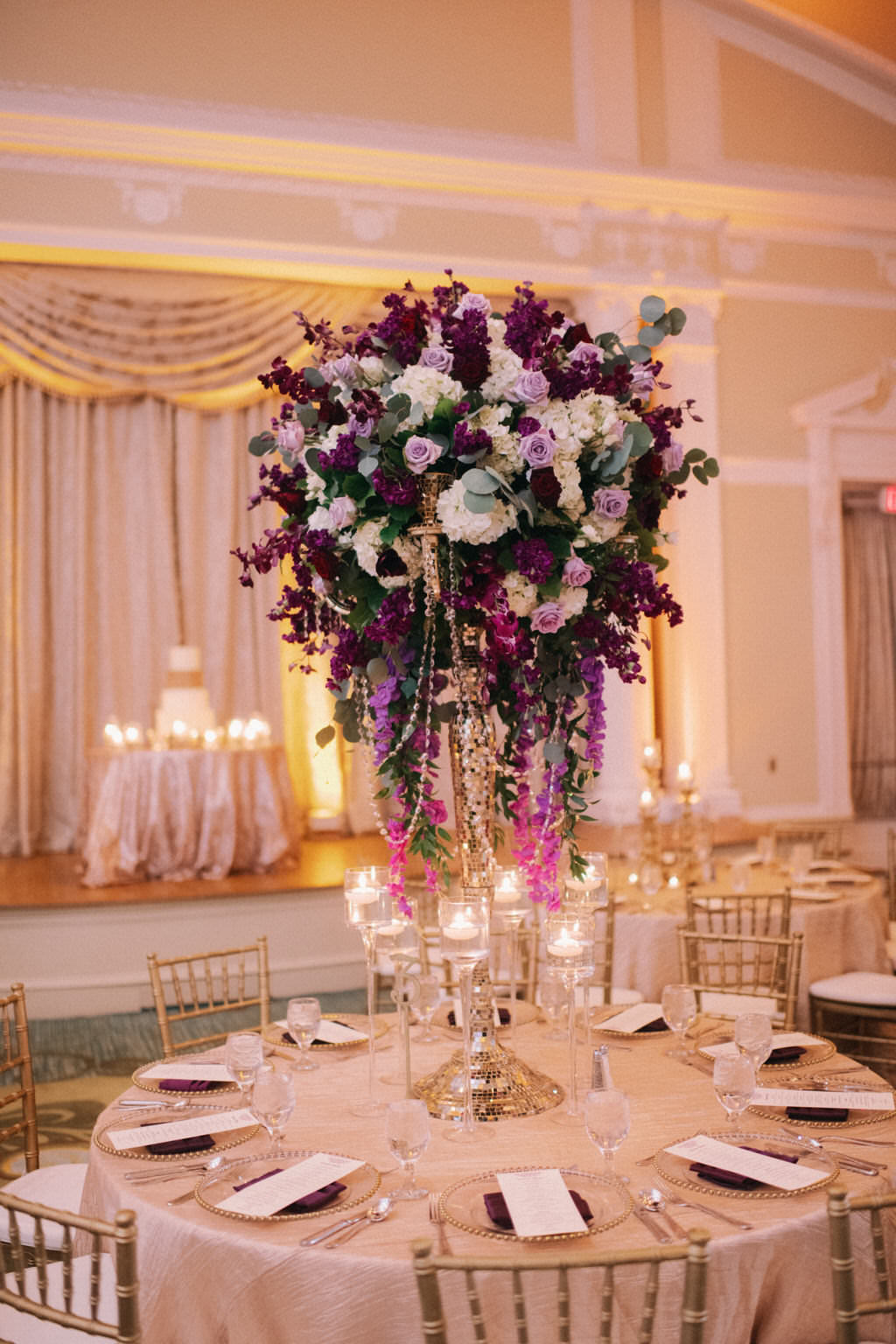 Elegant and Luxurious Wedding Reception Decor Portrait, Round Table with Gold Linen, Tall Purple, Plum, Lilac, Ivory and Hanging Amaranthus and Draped Crystals Floral Centerpiece