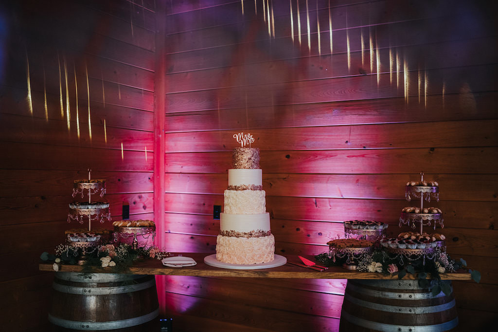 Elegant Five Tier White, Blush Pink Ombre Frosting Roses, Dark Pink Sparkle Top Tier and Embellishment Wedding Cake on Rustic Wooden Barrel Dessert Table with Pink Uplighting   Tampa Wedding Planner Kelly Kennedy Weddings and Events