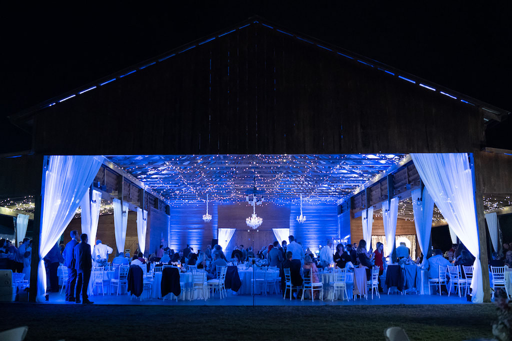 Rustic Barn Wedding Venue with Blue Uplighting and White Linen Draping and Crystal Chandeliers   Tampa Wedding Venue Rafter J Ranch   Wedding Planner Kelly Kennedy Weddings and Events