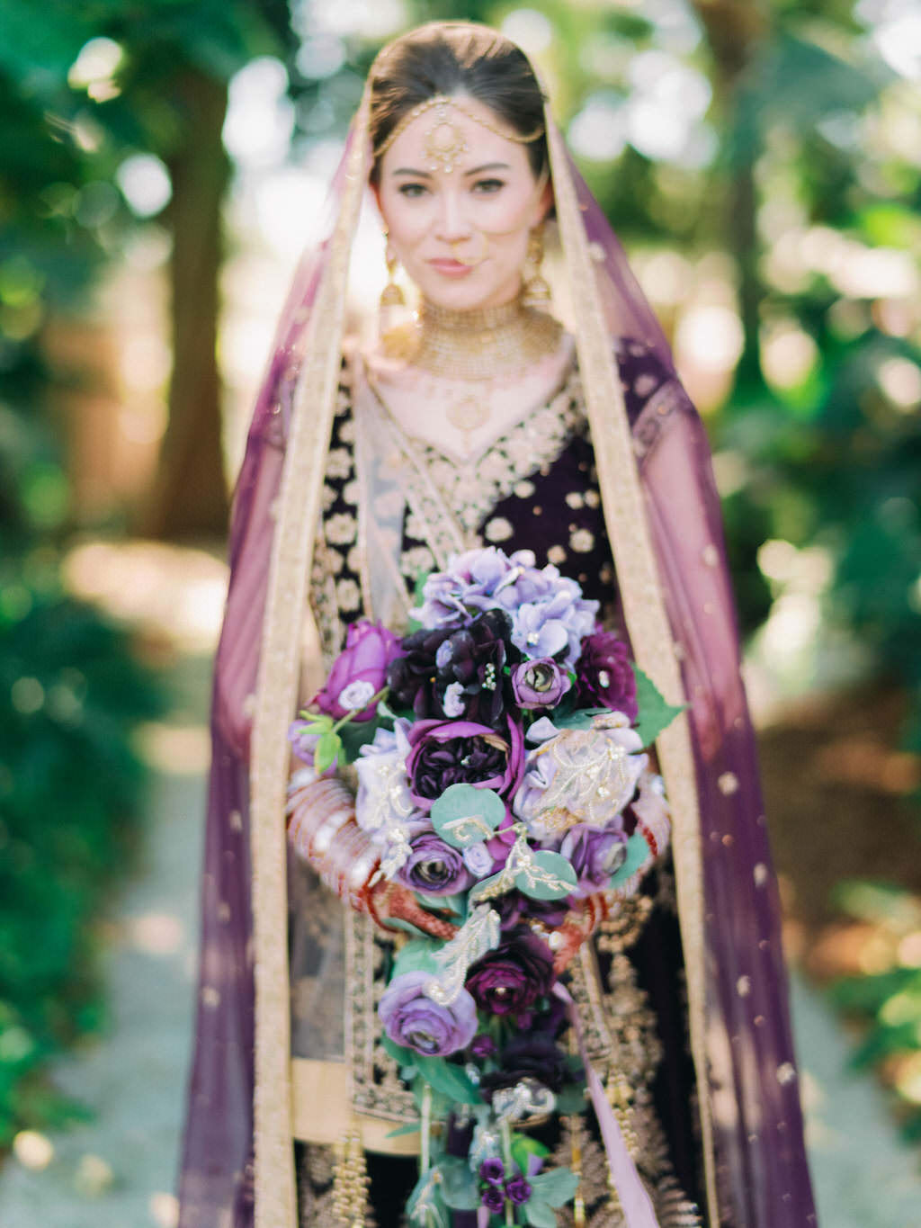 Tampa Traditional Hindu, Indian Colorful Bride, Beauty Wedding Portrait, Extravagant Gold Bridal Jewelry, Custom Purple Velvet and Gold Lehenga and Purple and Gold Bridal Indian Veil Holding Dark Purple, Plum, Lilac and Green Leaf with Gold Accent Floral Bouquet