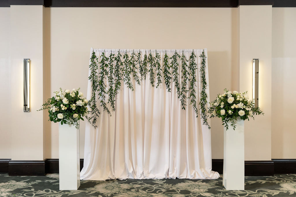 Classic Rustic Elegant Tampa Ballroom Wedding Ceremony Decor, White Drapery Backdrop Hanging Greenery, White Pedestals with Greenery and Ivory and White Roses Floral Arrangements | South Tampa Wedding Venue The Epicurean Hotel
