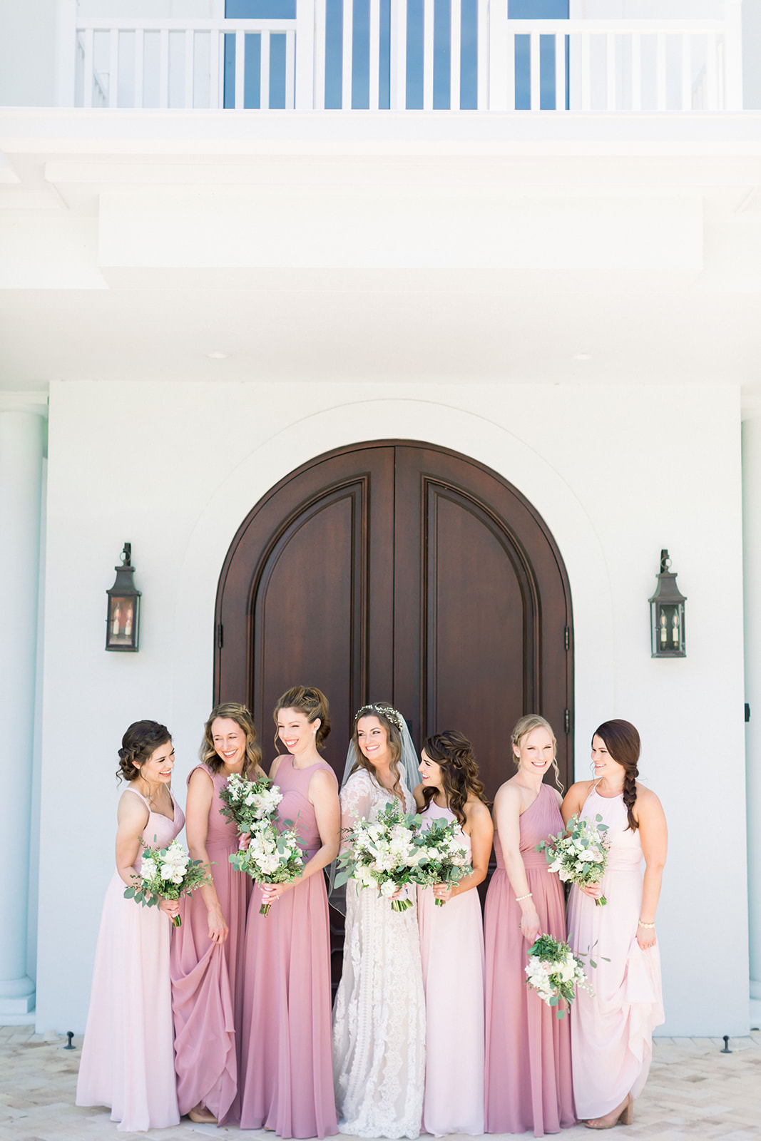 Florida Boho Inspired Bride and Bridesmaids Portrait, Wearing Mix and Match Blush, Pink Long Dresses, Holding White Floral Bouquets with Greenery | Tampa Bay Wedding Photographers Shauna and Jordon Photography | Tampa Bay Wedding Ceremony Venue Harborside Chapel