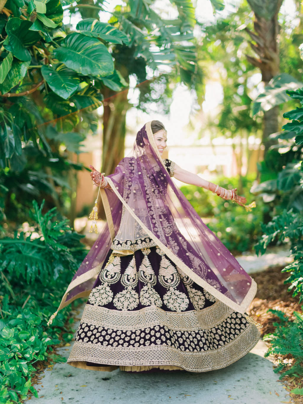 St. Pete Traditional Indian, Hindu Colorful Bride Fun Wedding Portrait Twirling in Custom Purple Velvet and Gold Lehenga and Purple and Gold Bridal Indian Veil