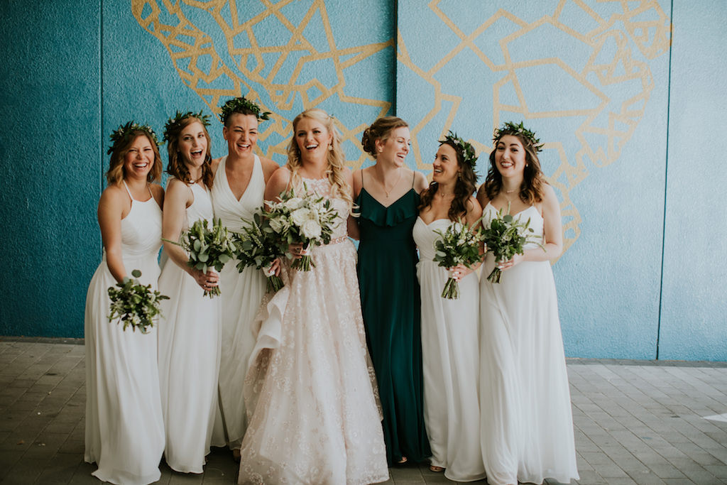 Florida Bride and Bridesmaids in Mix and Match White Long Floor Length Dresses with Greenery Crowns, Maid of Honor in Dark Green Dress, Bride in Lace High Halter Neckline and Illusion Wedding Dress Holding Organic Ivory and Greenery Floral Bridal Bouquet