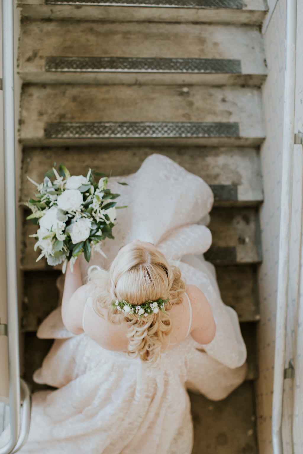 Creative Florida Bride Going Up the Stairs From Above Wedding Portrait Holding Organic Greenery and Ivory Floral Bridal Bouquet, Greenery Floral Hairpiece and Half Updo