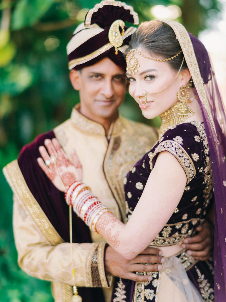 Traditional Indian Hindu Bride and Groom First Look Wedding Portrait, Groom in Black and Gold Sherwani Turban, Bride in Custom Purple Velvet and Gold Lehenga and Extravagant Gold Bridal Jewelry, Bridal Mehndi Henna Tattoo | Tampa Bay Bridal Hair and Makeup Artist Michele Renee The Studio