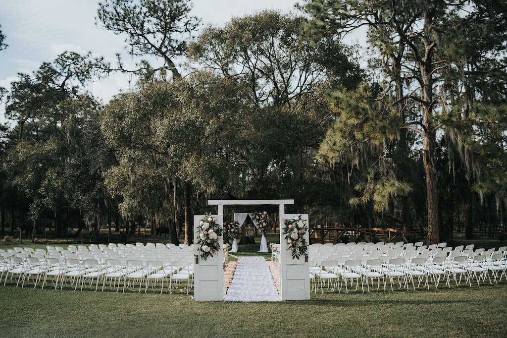Rustic Chic Outdoor Wedding Ceremony Decor, White Barn Doors with White and Greenery Floral Arrangements   Tampa Wedding Venue Rafter J Ranch   Tampa Bay Wedding Planner Kelly Kennedy Weddings and Events