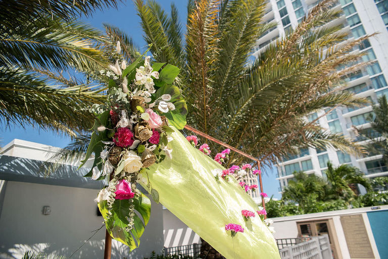 Tropical Elegant Wedding Ceremony Copper Arch with Monsterra Leaf and Pink, Cream, and Gold Roses with Carnations Dangling on Copper Pipe | Tampa Bay Wedding Florist Brides N Blooms Wholesale and Design