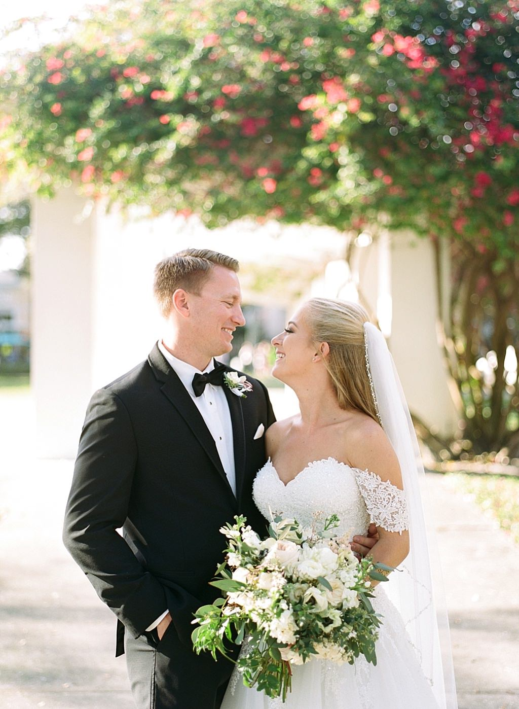 Tampa Elegant Bride in Sweetheart Off the Shoulder Lace Ballgown Wedding Dress Holding Garden Inspired White Roses, Anemone, Greenery Floral Bridal Bouquet and Groom in Black Tuxedo Wedding Portrait