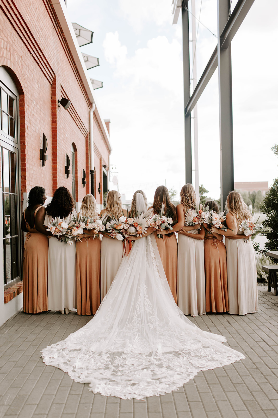 Creative Boho Bridal Party Portrait, Bridesmaids in Mix and Match Neutral and Sandy Blush Dresses Holding Palm Tree Leaves, Blush Pink Roses Floral Bouquet, Bride in Martina Liana Lace Wedding Dress with Romantic Cathedral Veil   Tampa Bay Industrial Wedding Venue Armature Works   Wedding Planner Coastal Coordinating