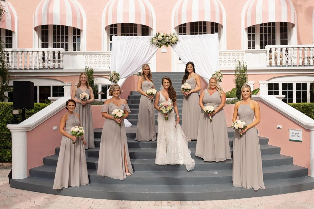 Florida Bridal Party, Bride and Bridesmaids holding Romantic White and Pink Floral Bouquet, Bride Wearing Hayley Paige Lace Overlay Fit and Flare Wedding Dress, Bridesmaids Wearing Long Beige Azazie Dresses | St. Pete Beach Historic Wedding Venue The Don CeSar Hotel