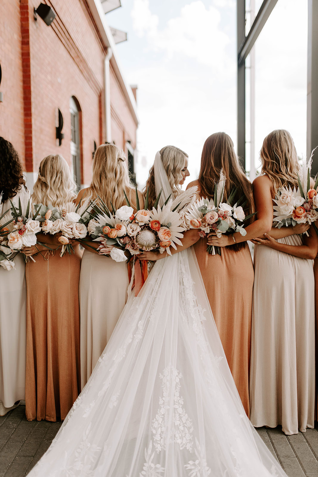 INSTAGRAM Creative Bridal Party Portrait, Bridesmaids in Mix and Match Neutral and Sandy Blush Dresses Holding Whimsical Palm Tree Leaves, Blush Pink and Burnt Orange Roses, King Protea Floral Bouquets, Bride in Romantic Cathedral Veil   Tampa Bay Wedding Planner Coastal Coordinating
