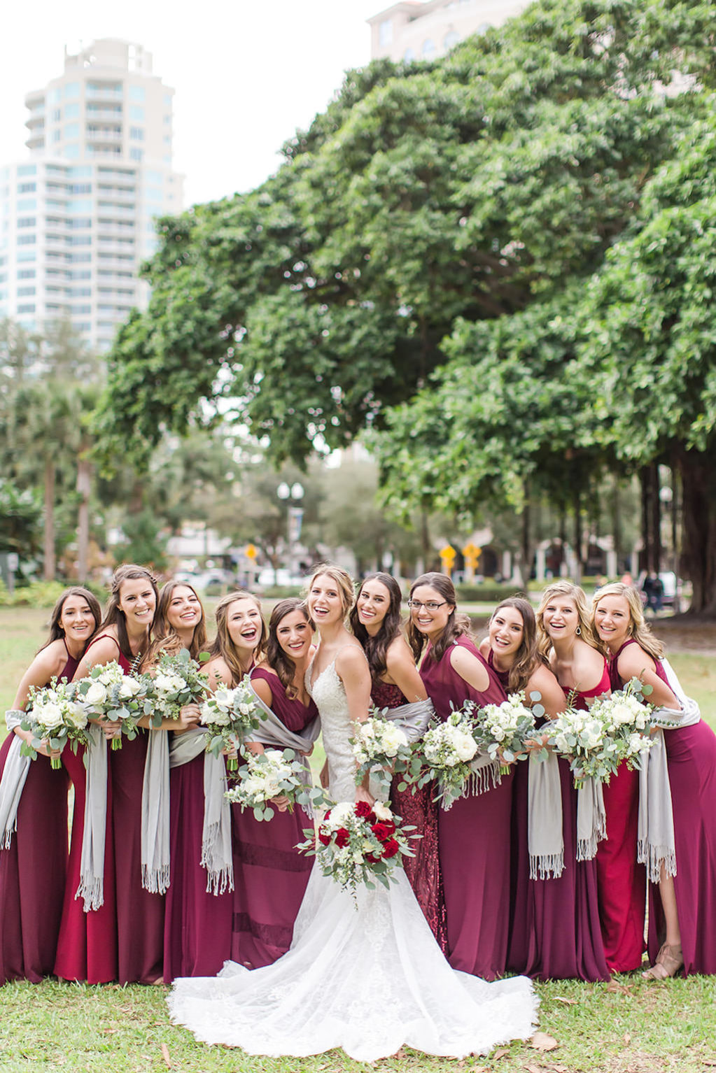 Christmas Inspired Bride and Bridesmaids, Long Garnet and Burgundy Dresses, Mix and Match Dresses Color and Style, Silver Shaw, Carrying Rustic White Bouquet with Greenery, in Downtown St. Pete Straub Park | Tampa Bay Wedding Photographers Shauna and Jordon Photography