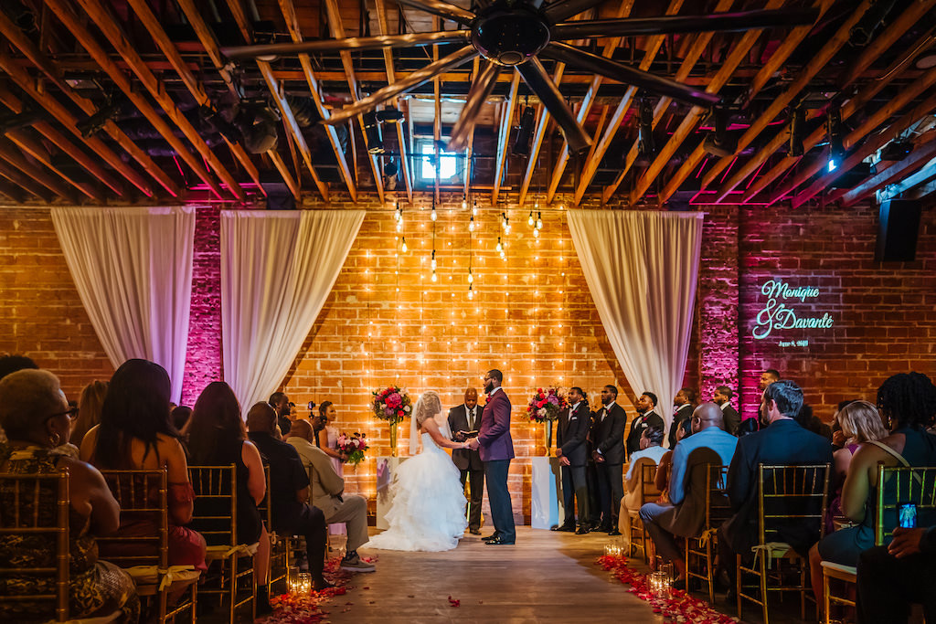 Florida Bride and Groom During Vow Exchange, Romantic Indoor Wedding Ceremony Decor, Exposed Red Brick Wall Ceremony Backdrop with Vintage Hanging Lights, White Draping, Gold Chiavari Chairs, Blush Pink Roses, Burgundy Flowers, Plum Hibiscuses, Quartz and Magenta Florals, Dark Greenery and Gold Centerpiece   Historic Tampa Bay Destination Industrial Wedding Venue NOVA 535, American Basketball Player Davante Gardner