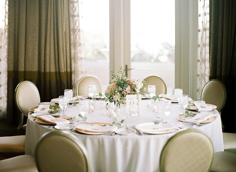Classic Formal Ballroom Wedding Reception Decor, Round Tables with White Linens, Gold Chargers, Blush Pink and White Roses, Eucalyptus and Greenery Low Floral Centerpiece with Gold Table Number Sign | Downtown St. Pete Wedding Venue The Birchwood