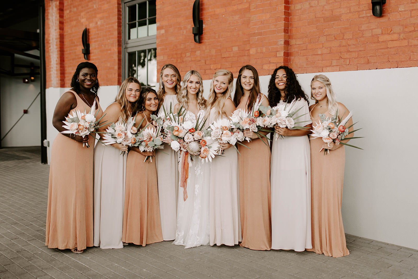 Boho Bridal Party Portrait, Bridesmaids in Mix and Match Neutral and Sandy Blush Dresses Holding Whimsical Palm Tree Leaves, Blush Pink and Burnt Orange Roses, King Protea Floral Bouquets   Tampa Bay Wedding Planner Coastal Coordinating