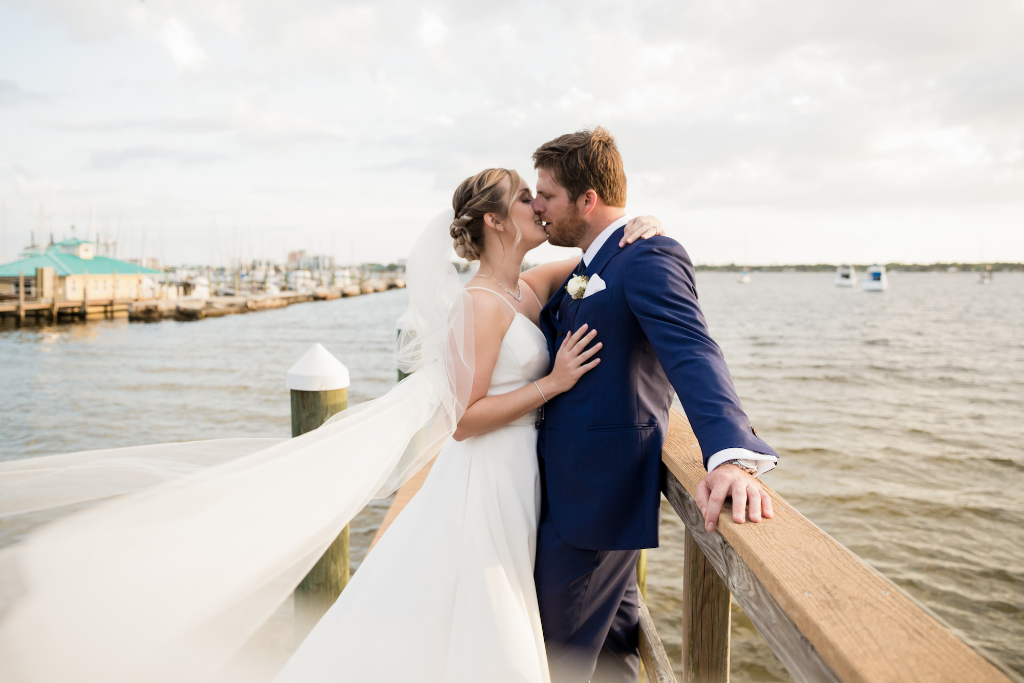 Classic Romantic Waterfront Wedding Portrait with Bride's Veil Blowing in the Wind