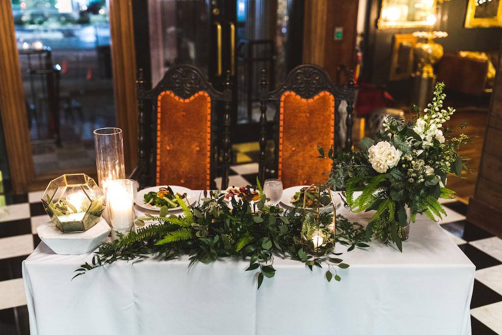 Romantic Modern New Years Eve Wedding Reception Decor, Sweetheart Table with White Linen, Greenery and White Roses Floral Arrangements, Gold Geometric Candle Holders, Antique Wood and Orange Velvet Chairs