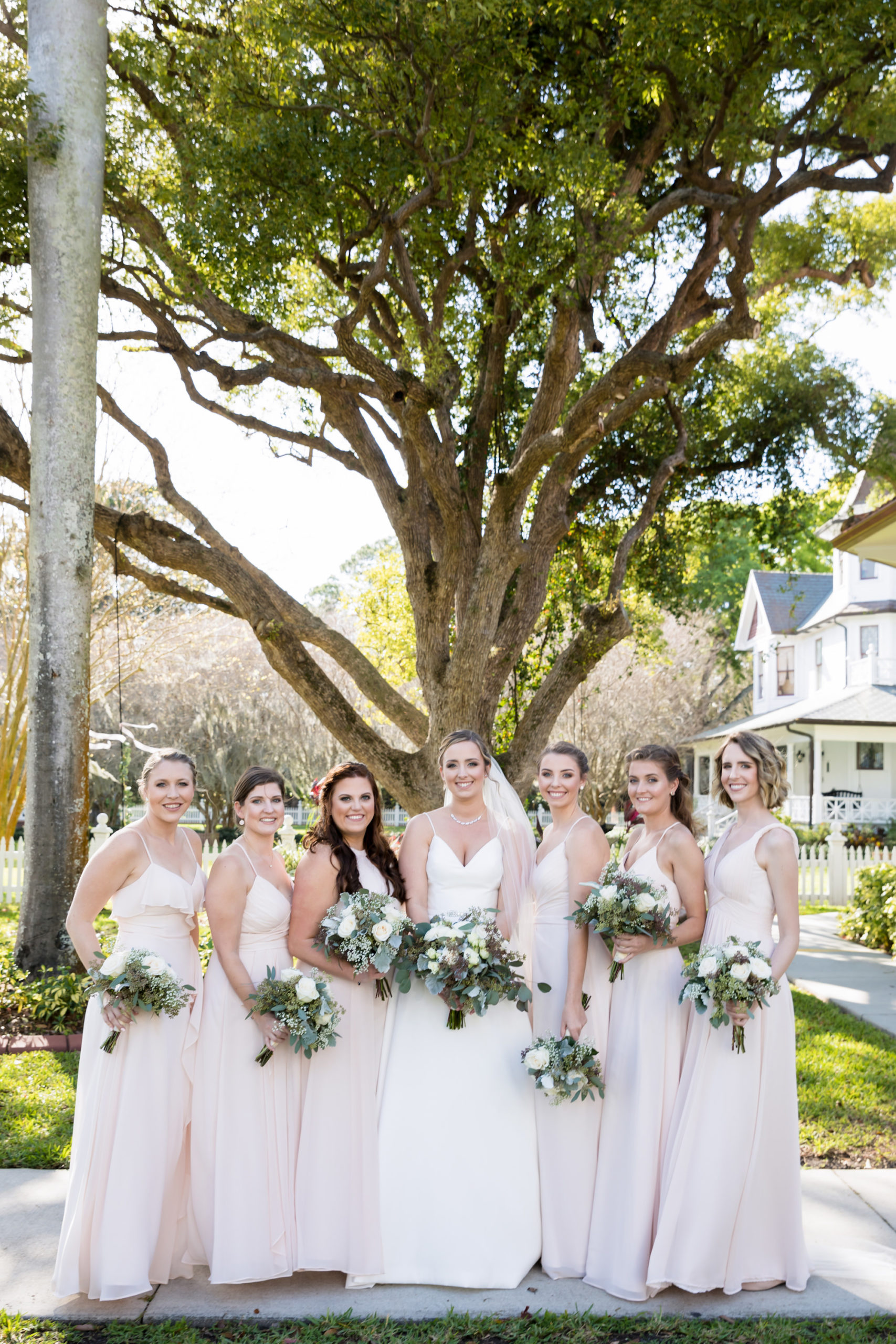 Tampa Bay Bridal Party, Bridesmaids in Mix and Match Blush Pink Dresses, Bride in Justin Alexander V Neck A-Line Wedding Dress Holding Organic Greenery and Ivory Floral Bouquets   Wedding Planner Coastal Coordinating