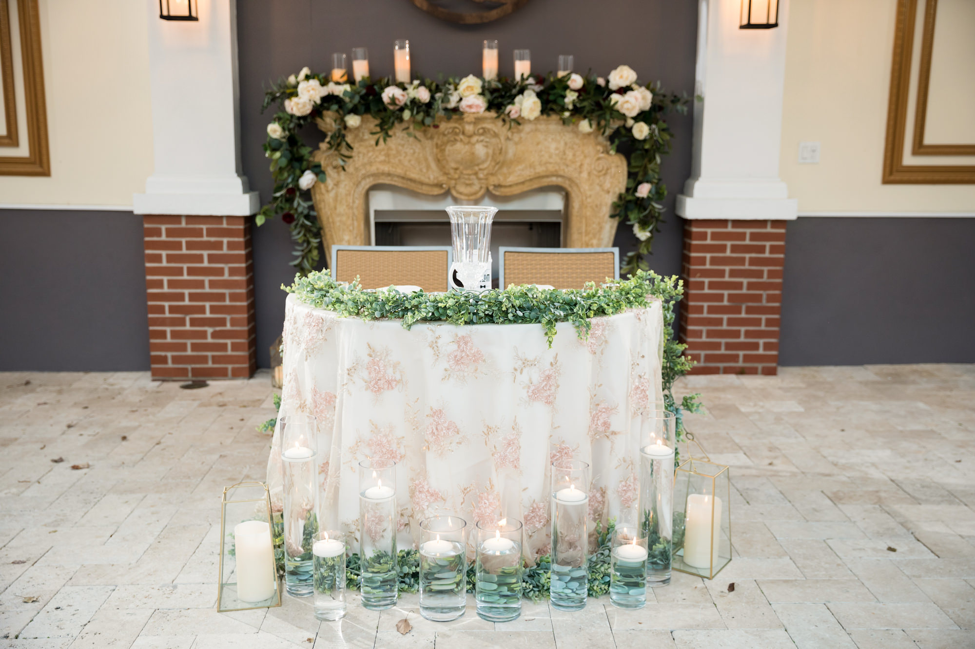 Classic Elegant Wedding Reception Decor, Sweetheart Table with Blush Pink Floral Linen, Floating Candles in High Low Hurricane Glass Vases, Greenery Garland, Ivory Roses, Fireplace Backdrop   Tampa Wedding Venue Palmetto Riverside Bed and Breakfast   Wedding Planner Coastal Coordinating