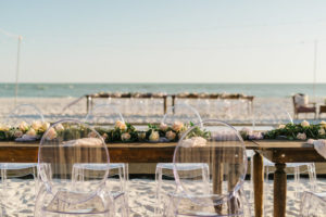Outdoor Beachfront Wedding Reception with Long Wooden Feasting Table and Ghost Chairs with Garland of Roses and Greenery | Resort at Longboat Key Club Sarasota Area Wedding Venue