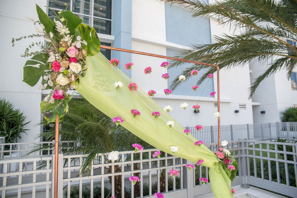 Colorful Tropical Wedding Ceremony Decor, Copper Arch with Lime Green Draping, Fuschia Pink and White Hanging Carnations, Ivory, Pink and Metallic Gold Painted Roses with Monstera Palm Leaves Floral Arrangement | Tampa Bay Wedding Photographer Kristen Marie Photography | Hotel Wedding Venue Hyatt Place Downtown St. Pete | Wedding Florist Brides N Blooms | Outside the Box Event Rentals