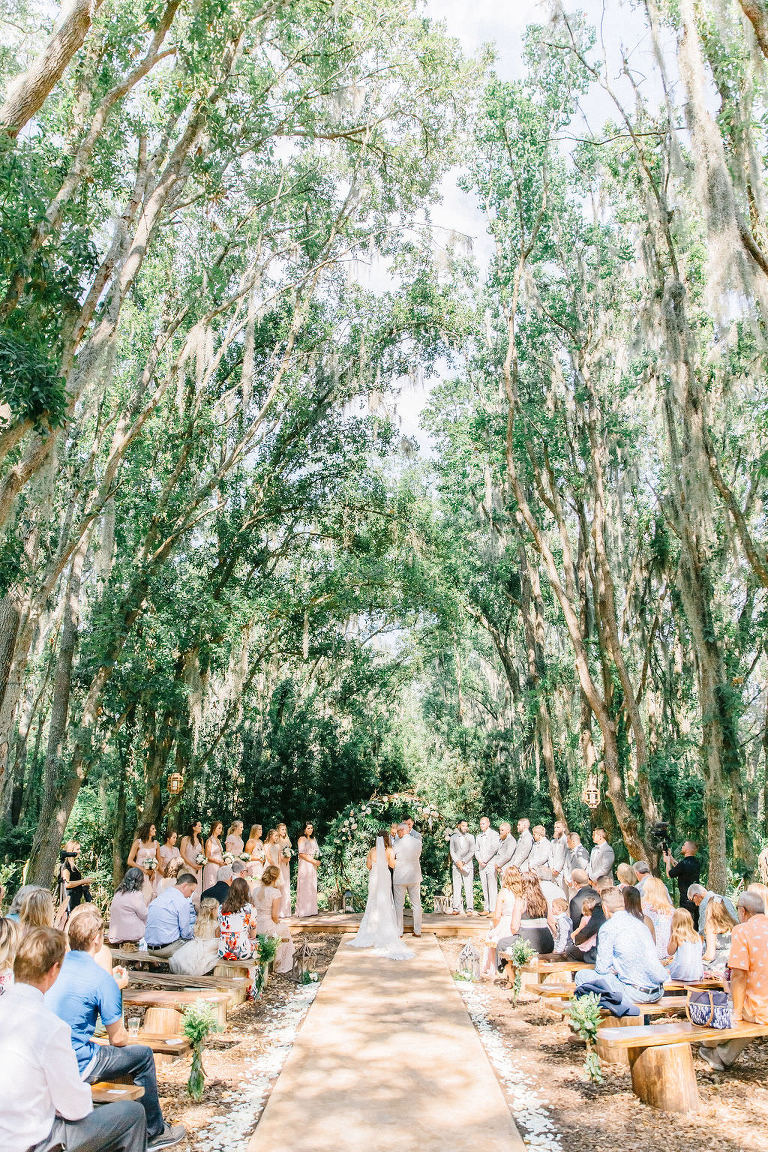 Enchanting Outdoor Wedding Under Canopy of Oak Trees, Bride and Groom Exchanging Wedding Vows During Ceremony Portrait | Whimsical Tampa Bay Venue Florida Rustic Barn Weddings