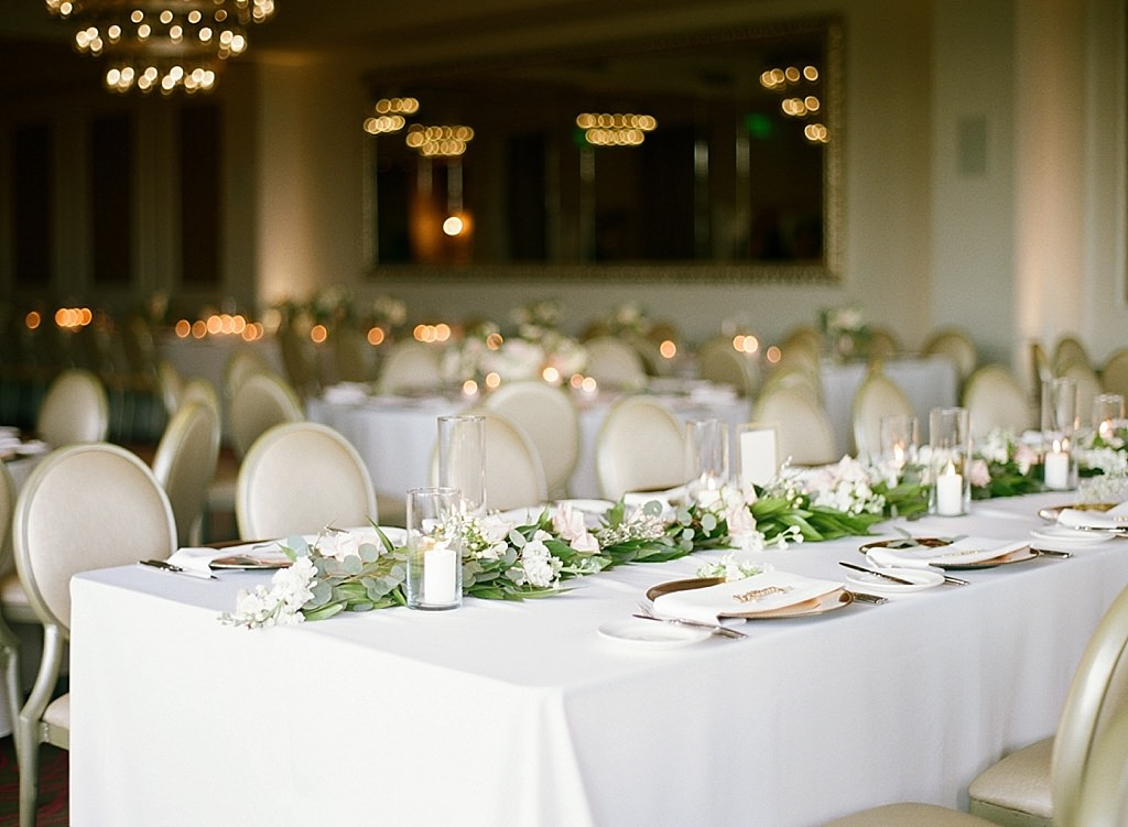 Formal Modern Wedding Reception Decor, Long Feasting Table with White Linen, Eucalyptus Greenery Garland, White Rose Florals, Gold Chargers and Glass Hurricane Candles | Downtown St. Pete Ballroom Wedding Venue The Birchwood