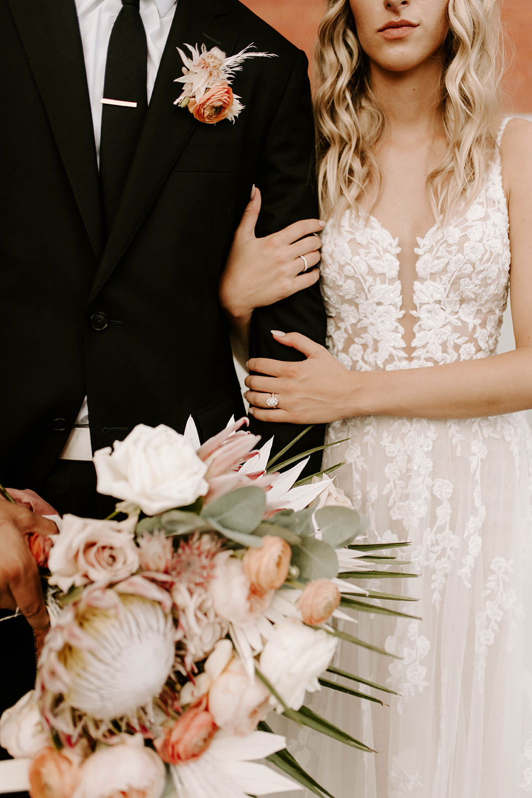 Boho Bride and Groom Creative Portrait, Groom Holding Bride's Whimsical Blush Pink and Burnt Orange Roses, Palm Tree Leaves, King Protea and White Roses Floral Bouquet