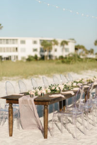 Outdoor Beachfront Wedding Reception with Long Wooden Feasting Table and Ghost Chairs | Resort at Longboat Key Club Sarasota Area Wedding Venue