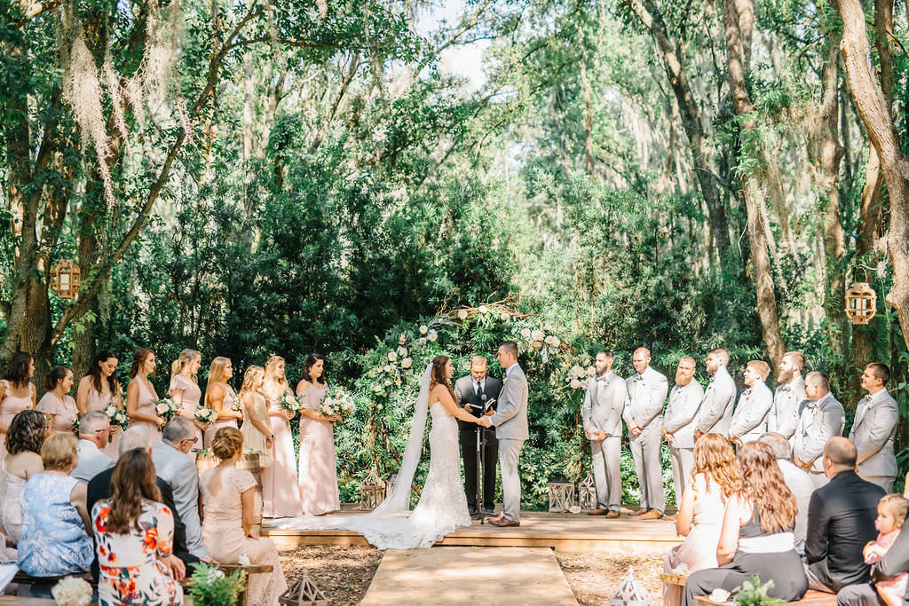Enchanting Outdoor Wedding Ceremony Under Canopy of Oak Trees, Bridal Party at Alter, Bride and Groom Exchanging Wedding Vows Portrait | Whimsical Tampa Bay Venue Florida Rustic Barn Weddings