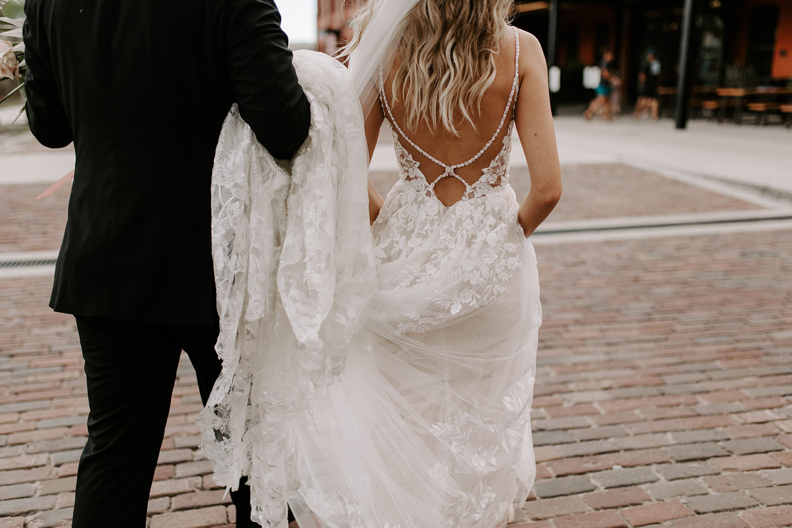 Creative Artsy Bride and Groom Portrait From Behind, Groom Holding Bride's Open Back with Rhinestone Straps Lace and Tulle Martina Liana Wedding Dress