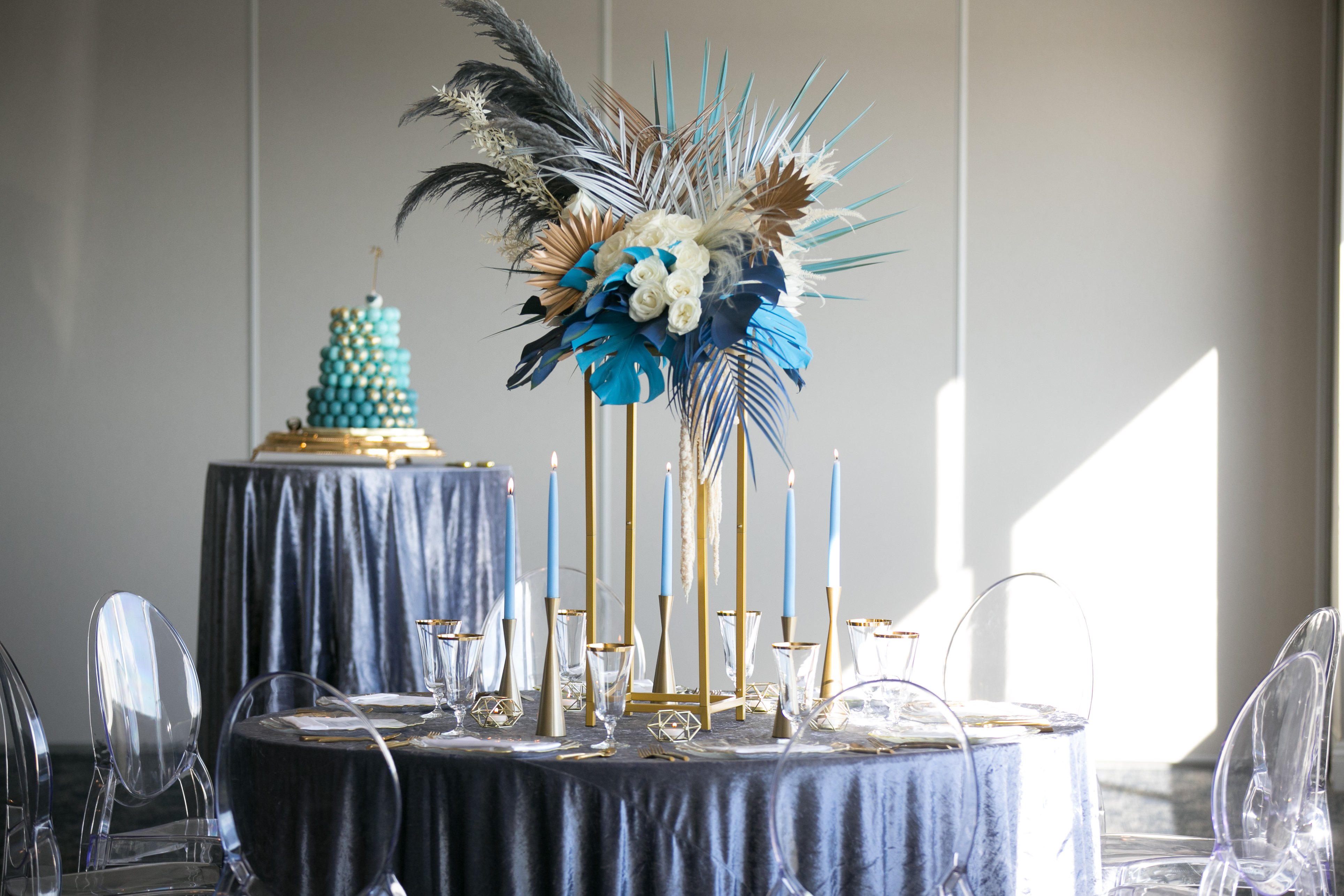 Whimsical Unique Tropical Wedding Reception Decor, Round Tables with Midnight Blue Linen, Tall Gold Candlesticks with Blue Candles, Tall Gold Geometric Stands with White Roses, Blue Monstera and Palm Tree Leaves and Feathers and Ghost Chair Seating | Tampa Wedding Chair Rentals Gabro Event Services | Velvet Navy Blue Table Linens Kate Ryan Event Rentals | Wedding Photographer Carrie Wildes Photography | Wedding Planner and Florist John Campbell Weddings | Tampa Wedding Venue Centre Club