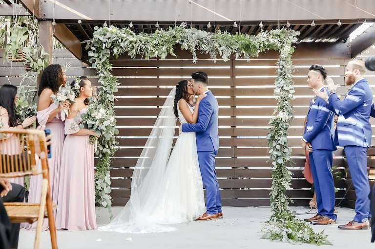 Florida Bride and Groom Exchanging First Kiss Wedding Ceremony Portrait Under Greenery Adorned Arch | Tampa Bay Wedding Photographer Lifelong Photography Studio | Wedding Planner Special Moments Event Planning | Unique Wedding Ceremony Venue Fancy Free Nursery