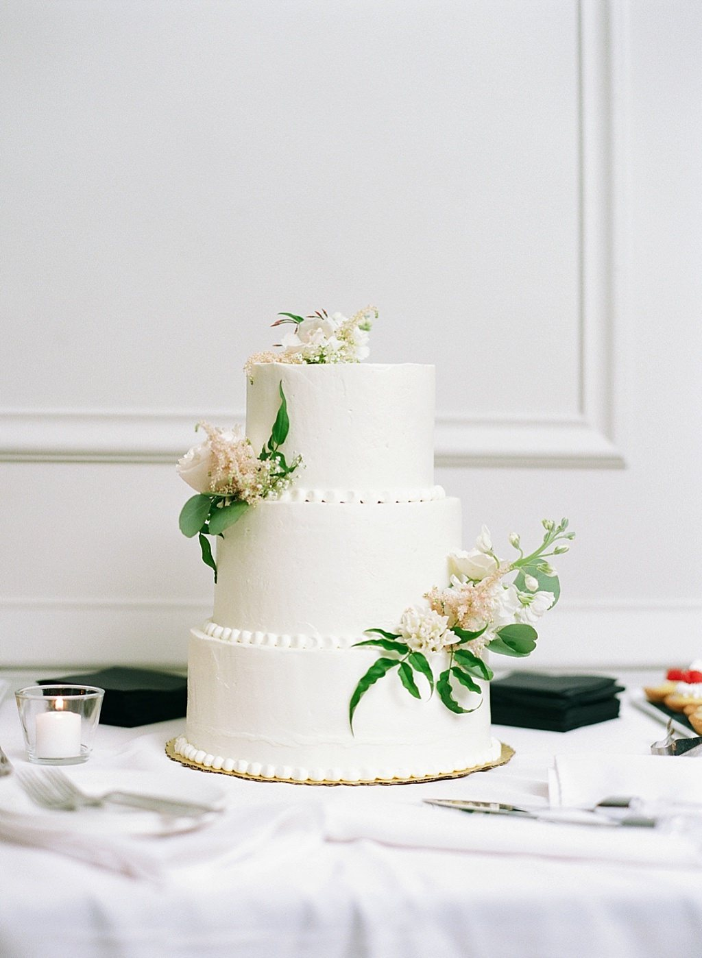 Modern Classic Smooth White Three Tier Wedding Cake Adorned with Greenery and Ivory Florals