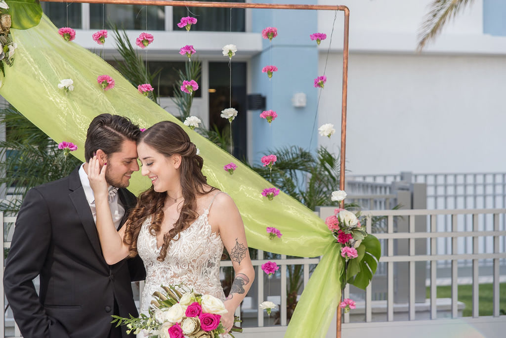 Modern Bride in Low V Neckline Lace and Illusion with Spaghetti Strap Wedding Dress and Groom in Black Tuxedo Wedding Portrait, Colorful Tropical Wedding Ceremony Decor, Copper Arch, Fuschia Pink and White Hanging Carnations, Lime Green Draping, Pink and Ivory Roses, Monstera Palm Leaf Floral Arrangement | Tampa Bay Wedding Photographer Kristen Marie Photography | Hotel Wedding Venue Hyatt Place Downtown St. Pete | Wedding Florist Brides N Blooms | Wedding Attire Nikki's Glitz and Glam Boutique | Outside the Box Event Rentals | Wedding Hair and Makeup LDM Beauty Group