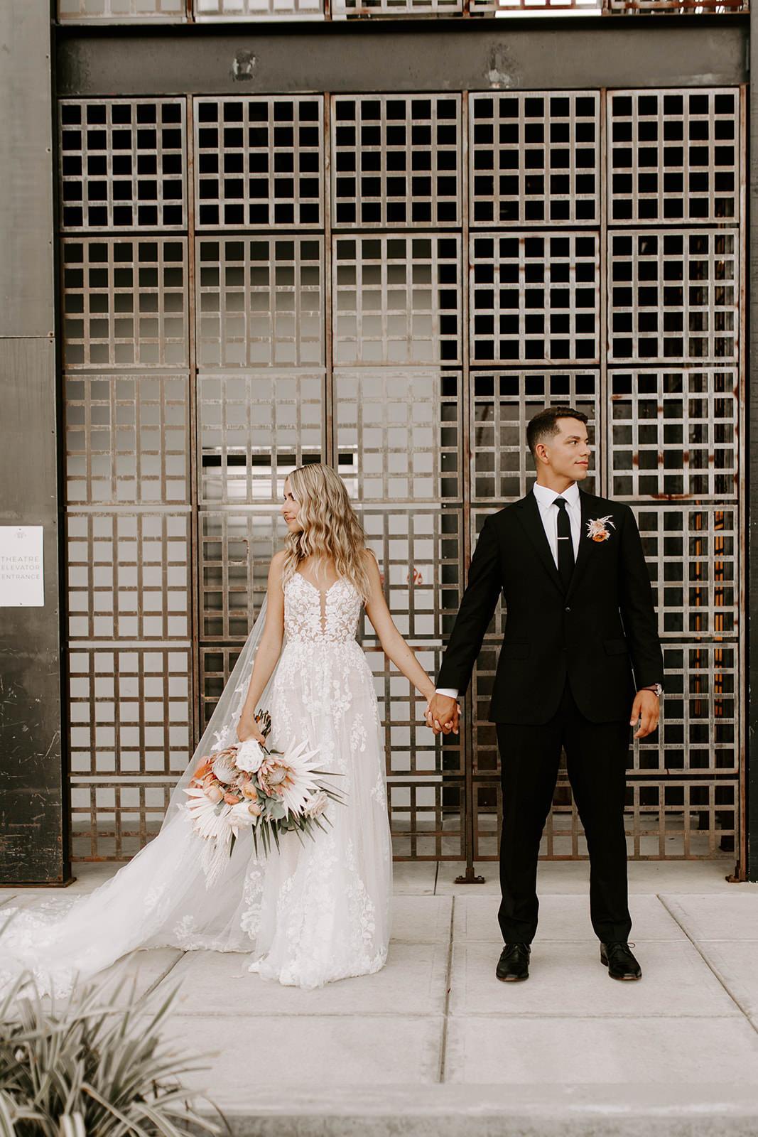 Boho Chic Bride and Groom Holding Hands Wedding Portrait