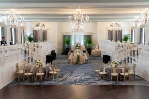 Elegant Summer Wedding in Two Tier Grand Ballroom, Gold Chiavari Chairs with Wedding Party Head Table, Round Tables with Silver and Gold Linens, Palm Leaf Decor, Low Floral Centerpieces with White and Blush Pink Flowers | Tampa Bay Historic Wedding Venue The Don CeSar on St. Pete Beach