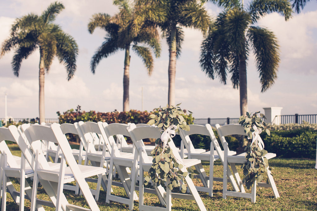 Rustic Chic Simple Tampa Bay Outdoor Garden Wedding Ceremony Decor Eucalyptus Leave Aisle Decor On White Folding Chairs Florida Wedding Photographer Luxe Light Images Waterfront Wedding Venue Tampa Yacht And