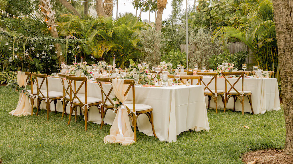 Tampa Garden Inspired Outdoor Wedding Reception Decor, Long Feating Tables, Ivory Linens, Wooden Cross Back Chair with Blush Pink Sashes and Greenery Ties