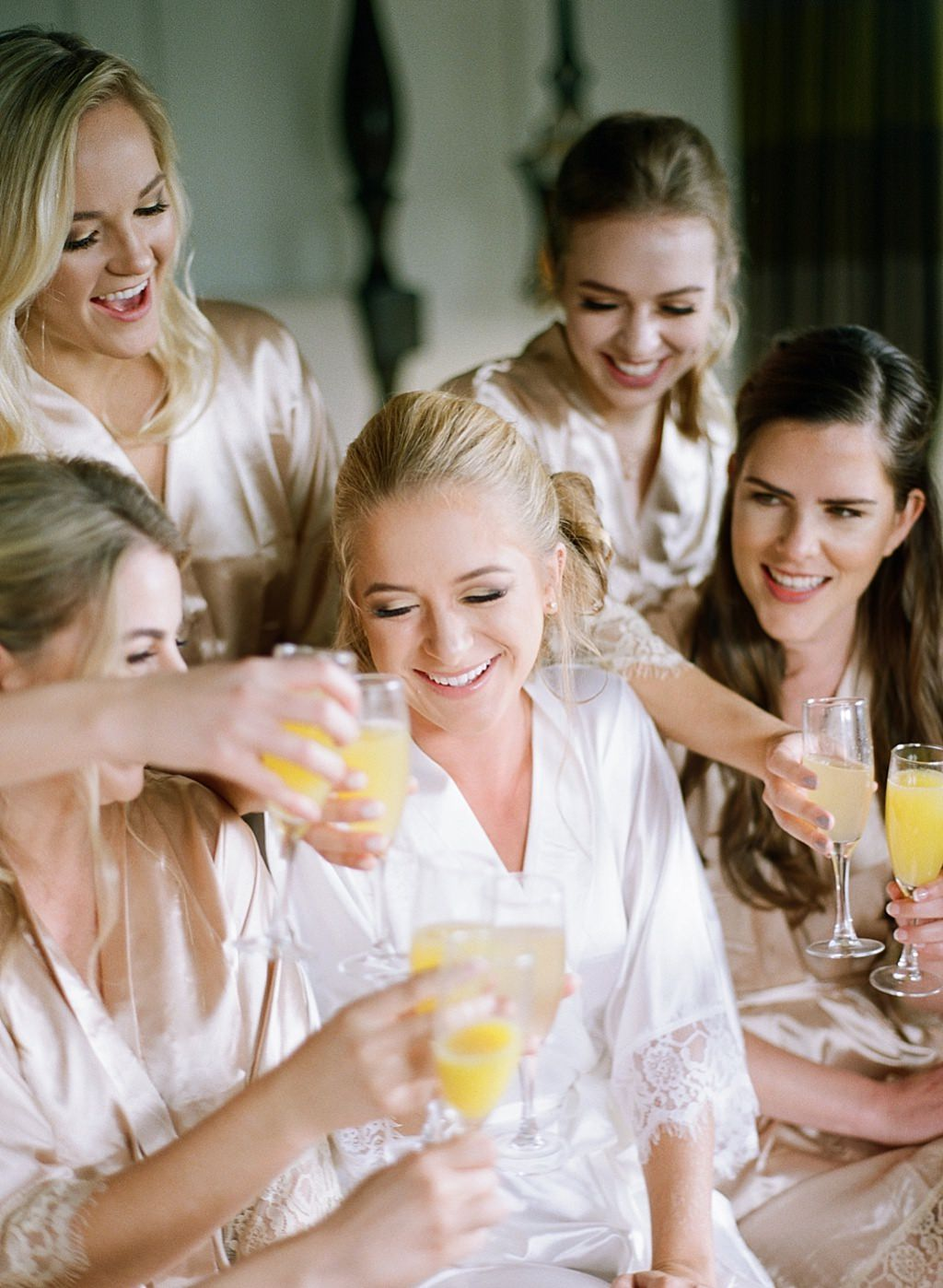 Tampa Bay Bride and Bridesmaids Cheering with Mimosas in Matching Champagne Gold Robes