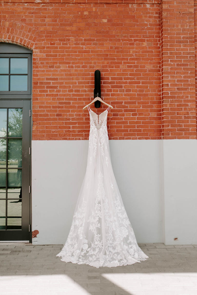 Boho Martina Liana Whimsical Lace and Tulle Open V Back A-Line Wedding Dress Hanging Outside Red Brick Industrial Building Tampa Wedding Venue Armature Works