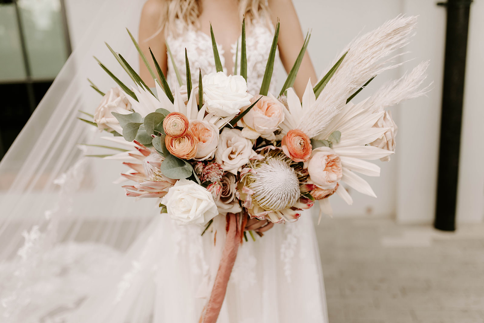 INSTAGRAM Boho Bride Holding Whimsical Palm Fronds, Eucalyptus, White Roses, Burnt Orange and Blush Pink Peonies, King Proteas and White Feathers Floral Bouquet   Tampa Bay Wedding Planner Coastal Coordinating