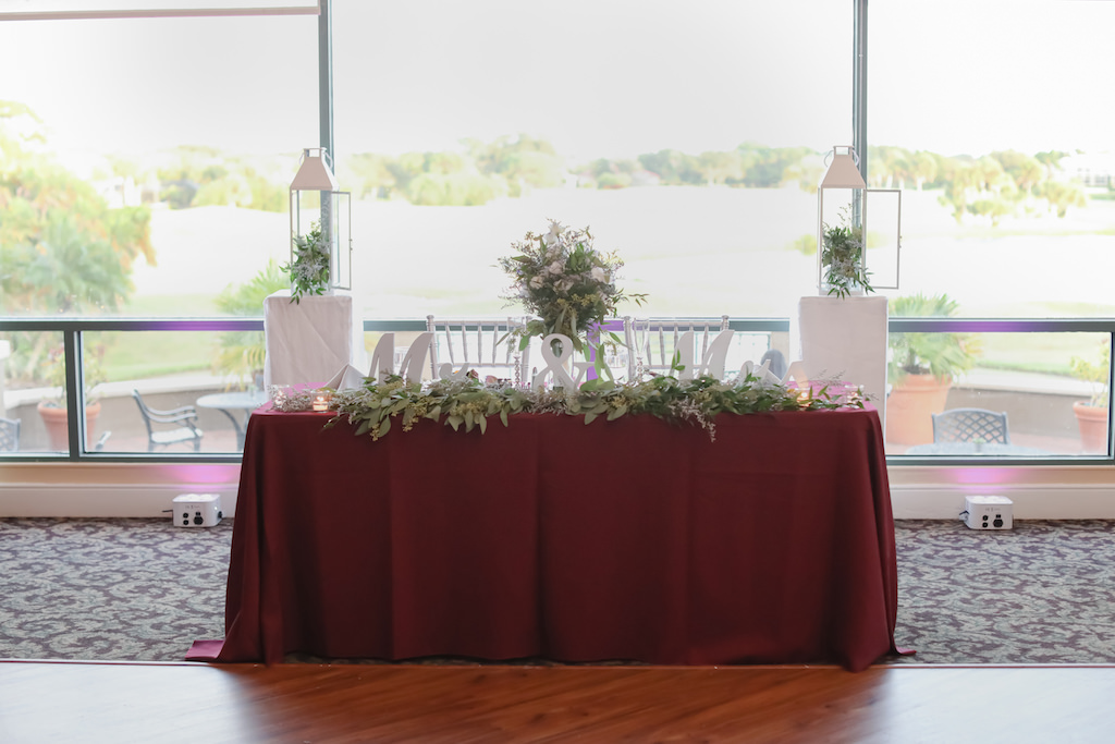 Mr. & Mrs. Sweetheart Table with Maroon Tablecloth and Greenery with Lanterns | Elegant Golf Course Ballroom Wedding Reception Venue with Floor to Ceiling Windows at The Bayou Club | Tampa Wedding Photographer Lifelong Photography Studio