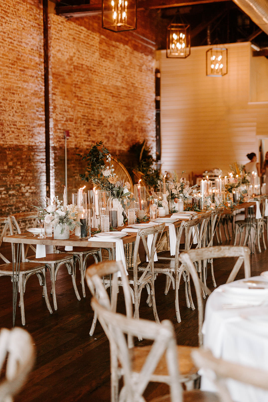 Boho Whimsical Wedding Reception Decor, Long Wooden Feasting Table with Floral Arrangements and Hurricane Glass Candle Holders, Wooden Crossback Chairs   Tampa Bay Wedding Planner Coastal Coordinating   Industrial Wedding Venue Armature Works