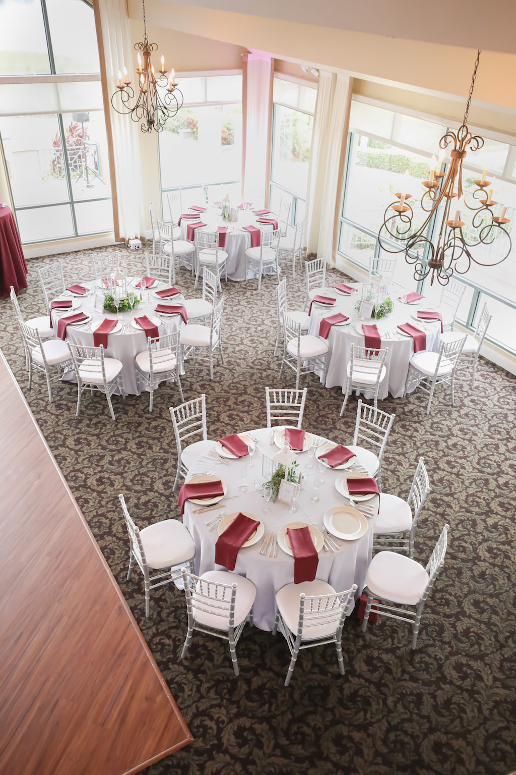 Winter Wedding Decor with Silver Chiavari Chairs, Silver Tablecloths and Maroon Napkins | Elegant Golf Course Ballroom Wedding Reception Venue with Floor to Ceiling Windows at The Bayou Club | Tampa Wedding Photographer Lifelong Photography Studio